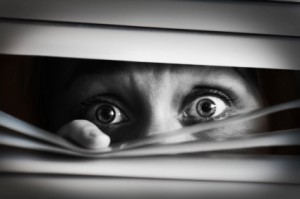 Scared-woman-peering-through-blinds-1acdf1 (1)